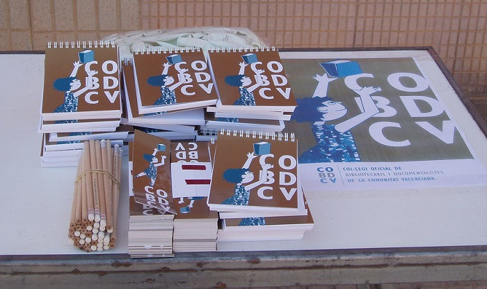 Foto de materiales promocionales del COBDCV (libretas, lápices, marcapáginas, cartel)