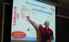 Foto de Julián Marquina señalando a la proyección de su presentación